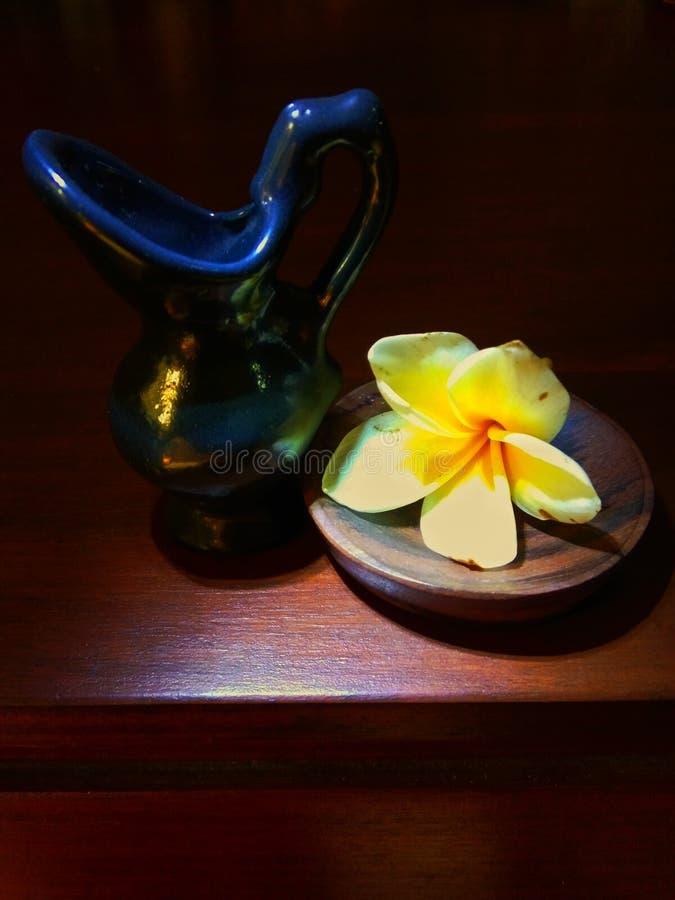 Litet keramiskt med frangipaniblommor arkivfoton