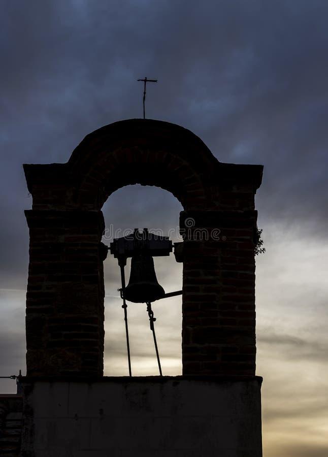 Litet klockatorn av en forntida italiensk kyrka i kontur mot en dramatisk himmel på solnedgången royaltyfri bild