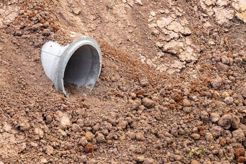 Litet konkret rör som begravas i sandig jord royaltyfri foto