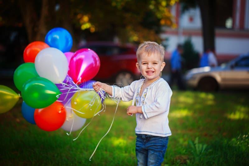 Litet le barn som rymmer gruppen av färgrika ballonger, royaltyfri foto