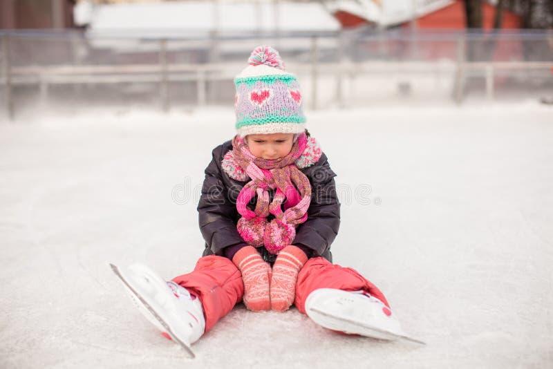 Litet ledset flickasammanträde på en åka skridskor isbana after fotografering för bildbyråer