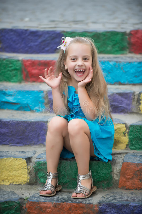 Litet lyckligt behandla som ett barn flickan i blåttklänning på färgrik trappa arkivbilder