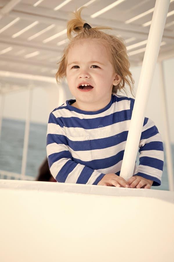 Litet lyckligt behandla som ett barn pojken på yachten i den marin- skjortan, mode fotografering för bildbyråer