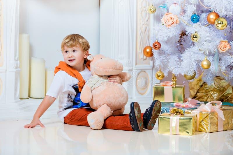Litet mycket gulligt blont pojkesammanträde vid spisen och viten Chr fotografering för bildbyråer