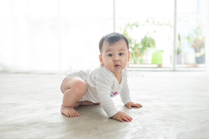 Litet nätt behandla som ett barn flickakrypning på golvet hemma arkivfoton
