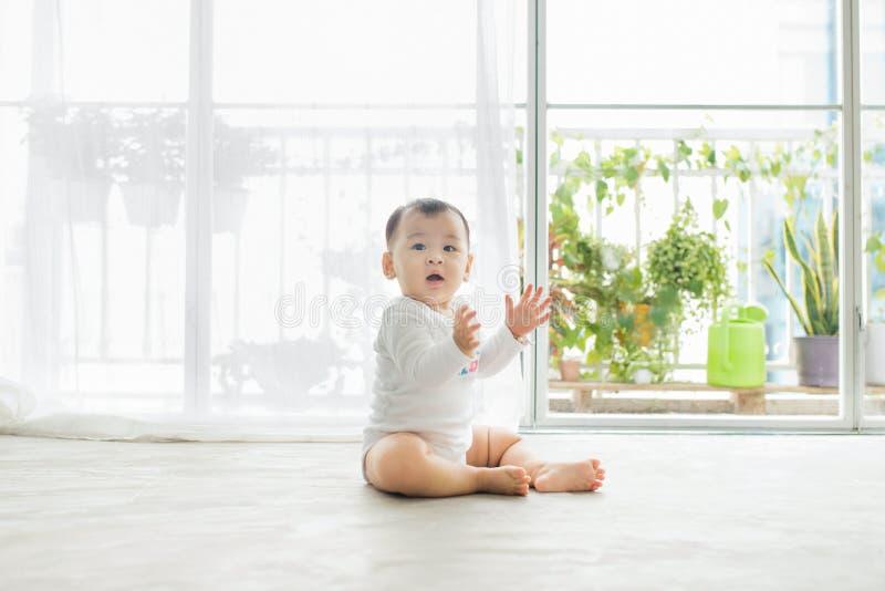 Litet nätt behandla som ett barn flickasammanträde på golvet hemma arkivfoton