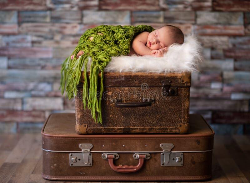 Litet nyfött behandla som ett barn att sova på lantliga resväskor arkivbild