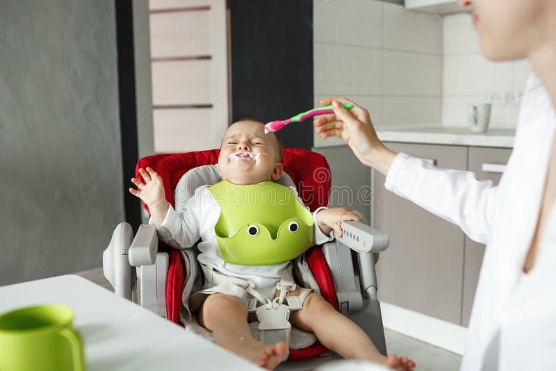 Litet nyfött behandla som ett barn sammanträde behandla som ett barn stol med near munskrik för rester och vägrar in att äta, med arkivfoton