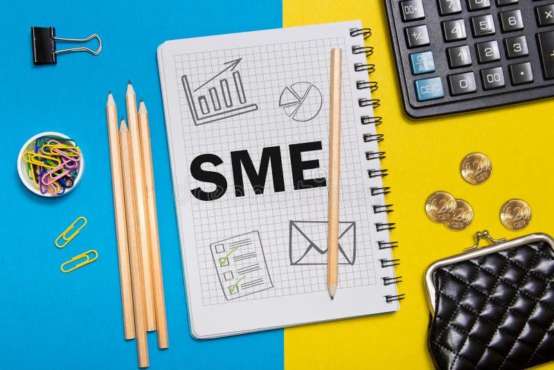 Litet och medelföretag, SME-anmärkningar i anteckningsboken på skrivbordet av en affärsman i regeringsställning AffärsidéSME royaltyfria bilder