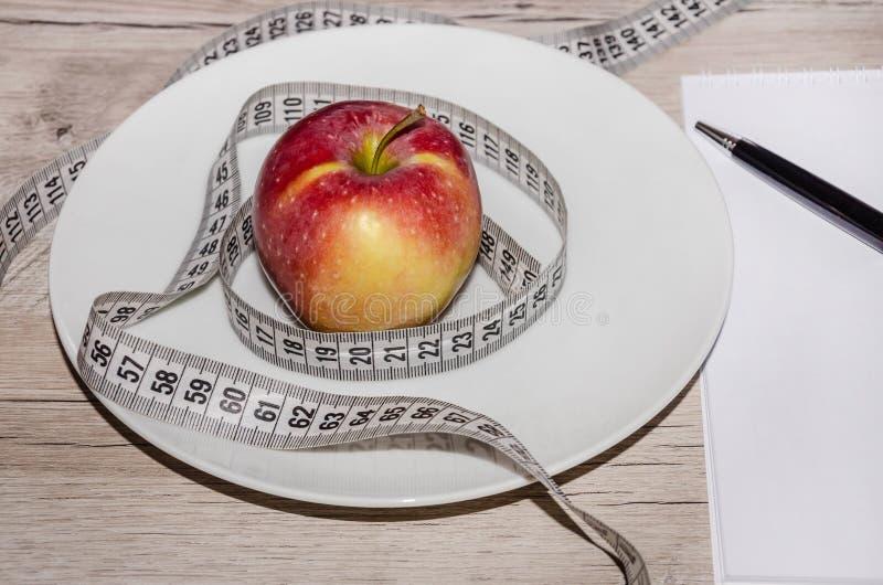 Litet rött äpple i en vit platta, anteckningsbok och penna på tabellen royaltyfria foton