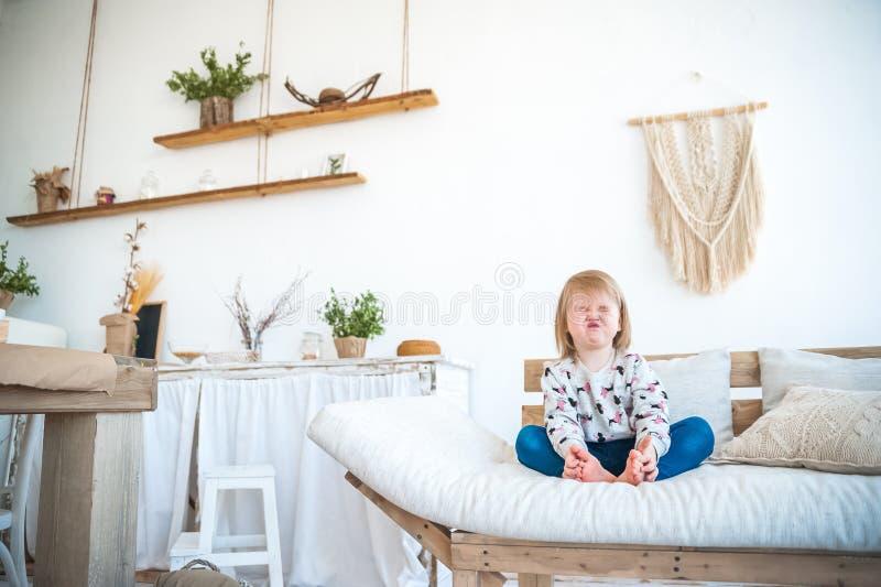 Litet roligt flickasammanträde i köket i en lantlig stil Tänd texturerat möblemang, soffan, tabellen, makramé på väggen Barnet royaltyfria foton