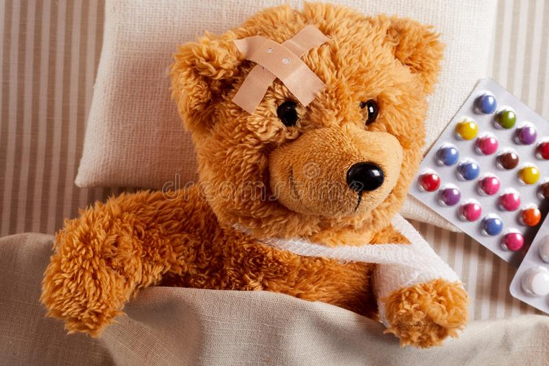 Litet sårat ligga för nallebjörn som är sjukt i säng arkivfoton