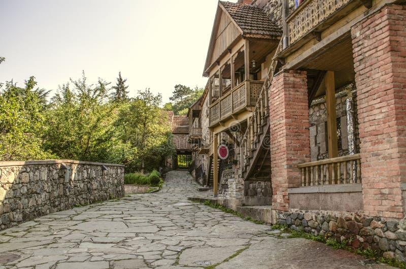 Litet shoppar på gatan Sharambeyan i gamla hus som göras av grova sten- och tegelstenkolonner, med träsned balkonger i Muen arkivfoton