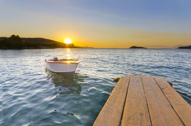 Litet skeppsdocka och fartyg på sjön på solnedgången royaltyfria foton