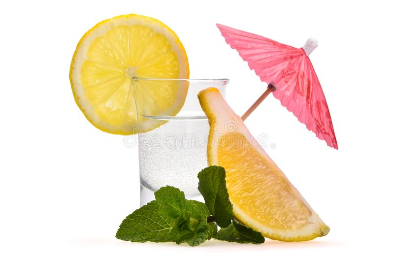 Litet skott med alkohol, pepparmintsidor, stycken av citronen och det dekorativa coctailparaplyet royaltyfri bild