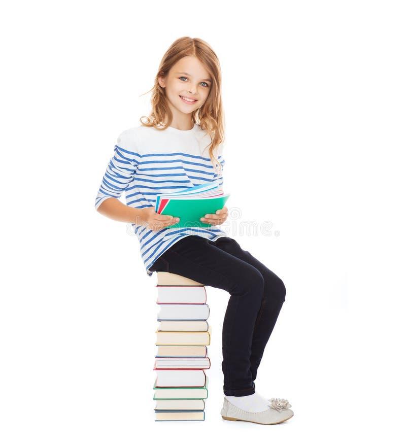 Litet studentflickasammanträde på bunt av böcker royaltyfri foto