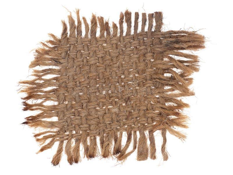 Litet stycke av gammal säckväv, hessianstyg med slitna kanter som isoleras på vit Gammalt, slitet och bränt sackcloth royaltyfri bild