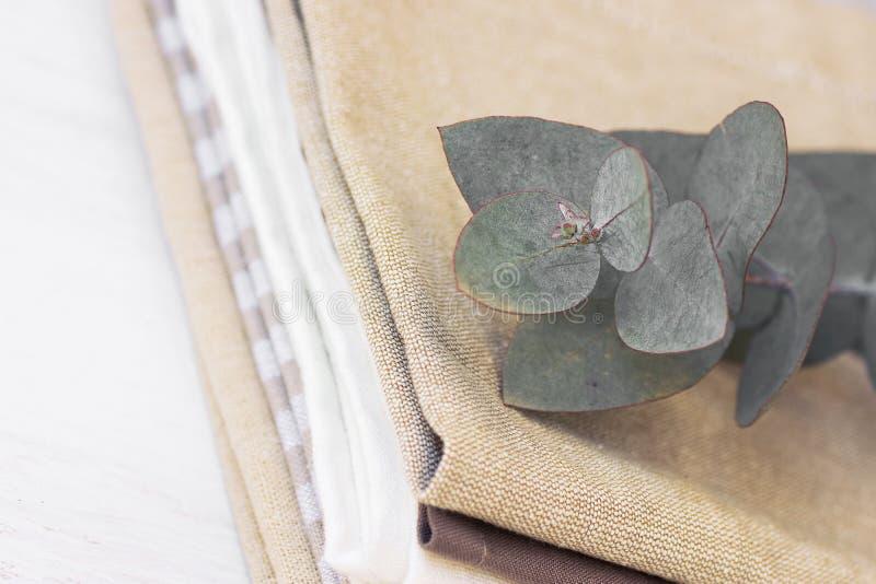 Litet suddig bakgrund för hantverkköktextil Bunt av rena bomulls- och linnehanddukar och servetter med eukalyptusfilialen royaltyfri fotografi