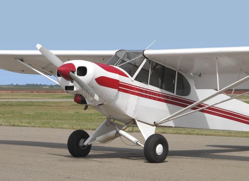 Litet svan-hjul rött och vitt flygplan. arkivbilder