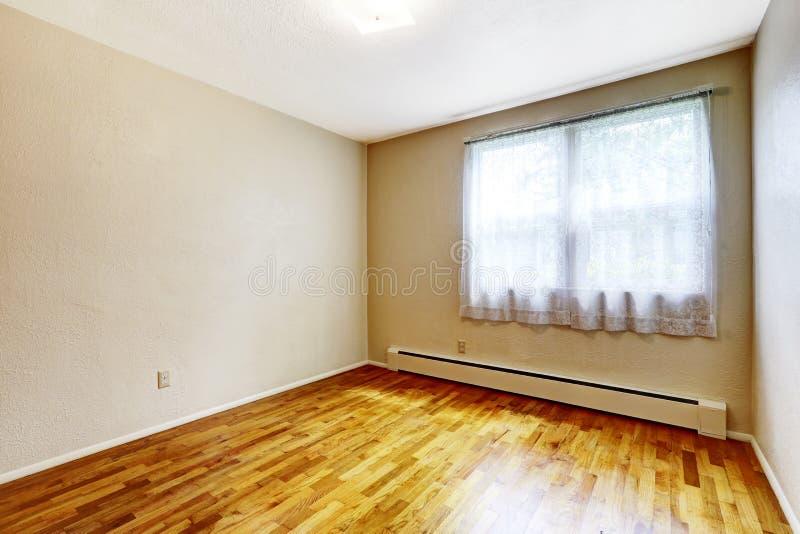 Litet tomt källarerum med väggar för ädelträgolv och beiga royaltyfria foton