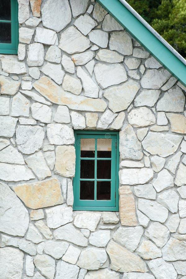 Litet träfönster i en stenstuga med grön klippning och gaveln royaltyfri bild
