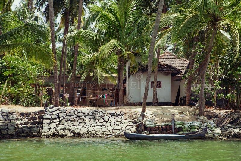 Litet traditionellt hus och gammalt fartyg på floden i Kerala, Ind arkivfoto