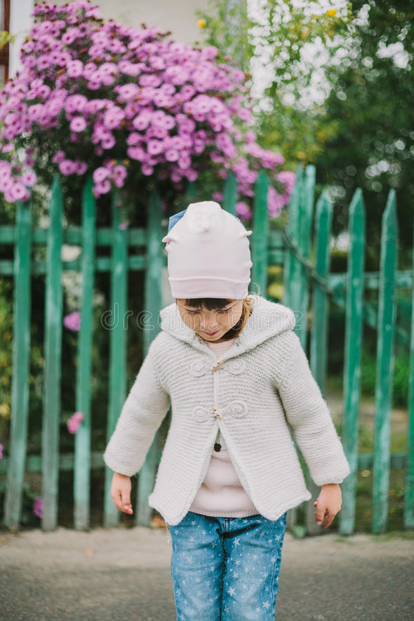 Litet ung flickaanseende nära den gröna staket- och lilafloen royaltyfria bilder