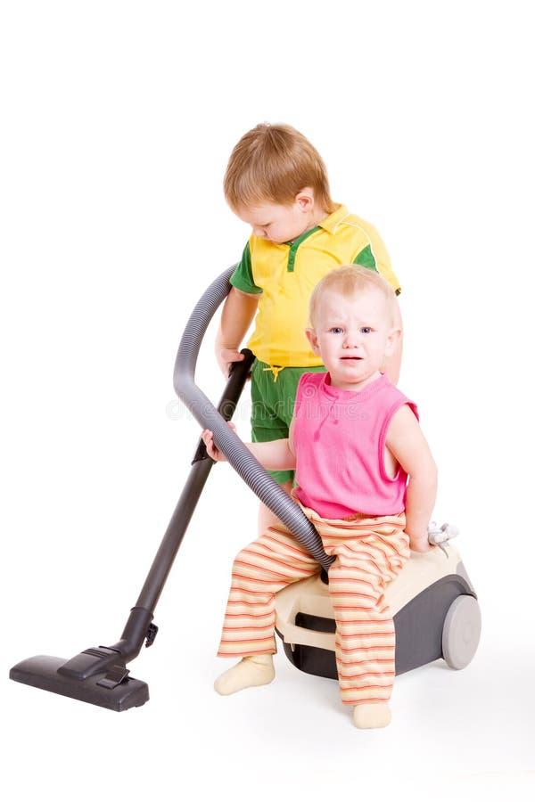 litet vakuum för pojkerengöringsmedelflicka arkivfoton