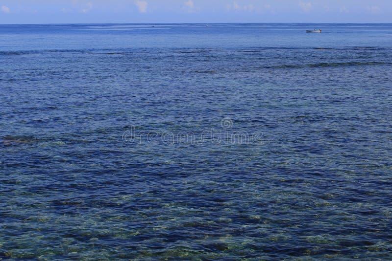 Litet vitt fartyg på drift i ett stort blått hav fotografering för bildbyråer