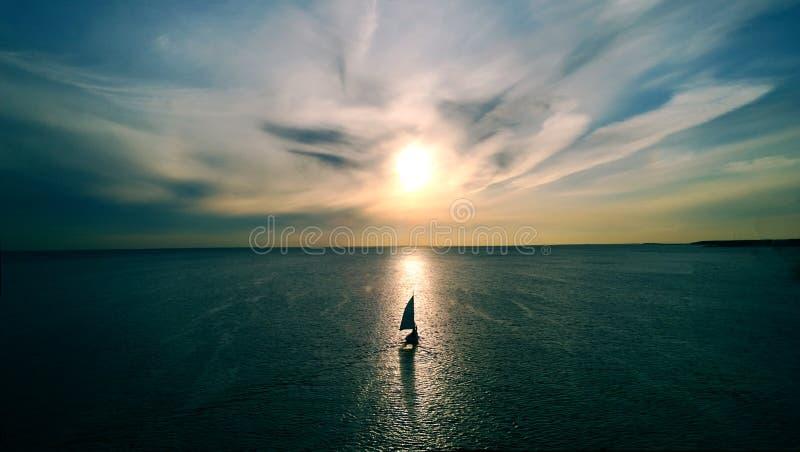 Litet vitt fartyg som svävar på vattnet in mot horisonten i strålarna av inställningssolen Härliga moln med gul viktig royaltyfri fotografi