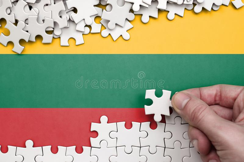 Lithuania flag is depicted on a table on which the human hand folds a puzzle of white color stock photography