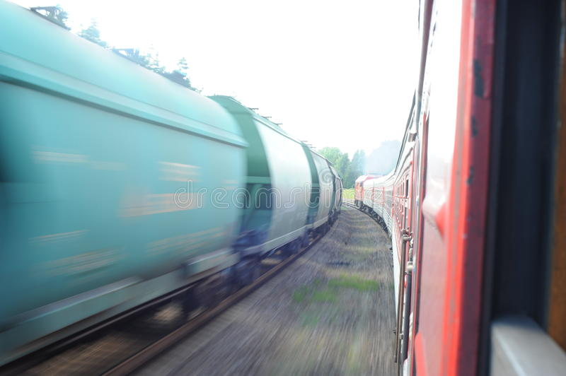 Lithuania Railway Network and Track. Going on Fast Train. Leaving Station. Blurry Train on Oposite Side. Lithuania Railway Network and Track royalty free stock photo