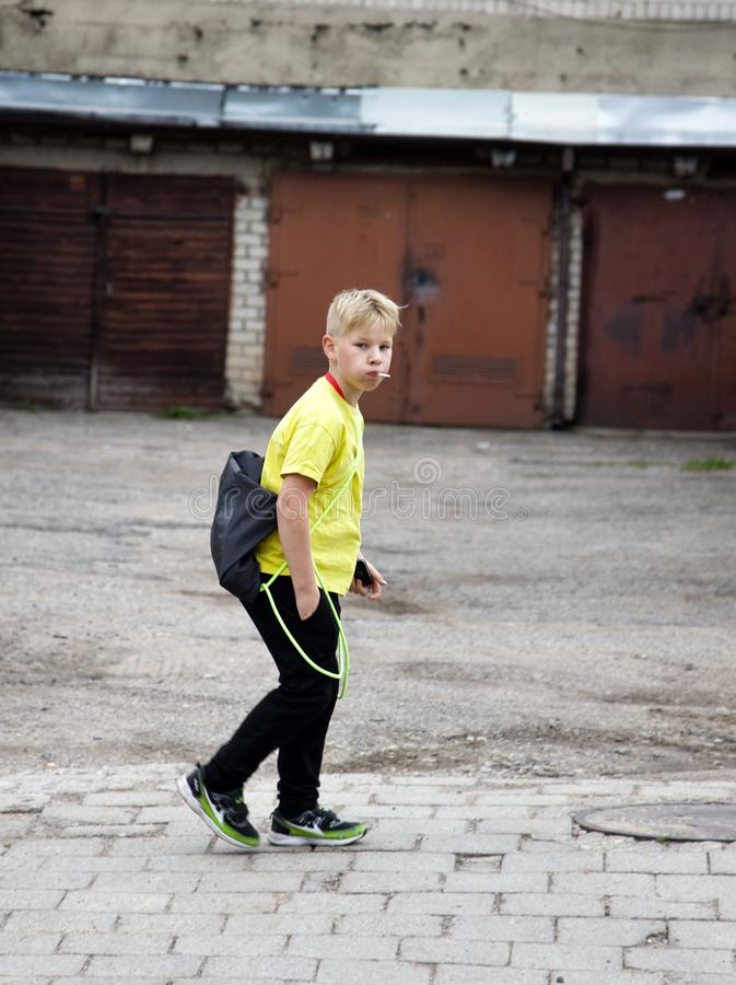 Fashionable boy in yellow. Lithuania, Vilnius - September 6, 2017: Fashionable boy in yellow with a Lollipop in his mouth royalty free stock photography