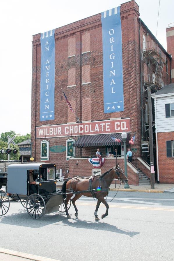LITITZ, PA - 30. AUGUST: Amisches Pferd und verwanztes Reiten hinter berühmten Wilbur Chocolate Company hat auf Weg 501 Hauptsitz lizenzfreies stockbild