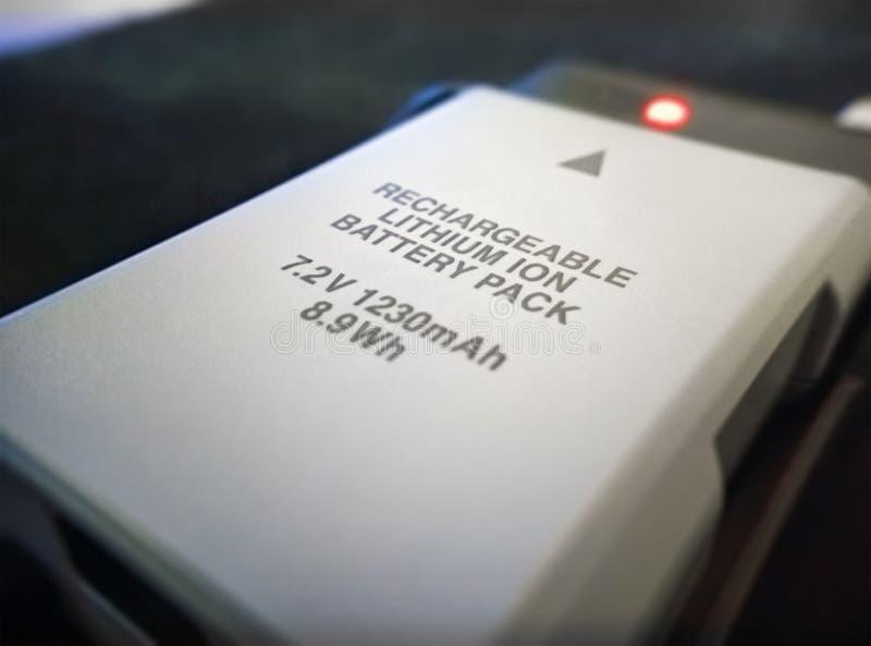 Litium Ion Rechargeable Battery på en uppladdare fotografering för bildbyråer