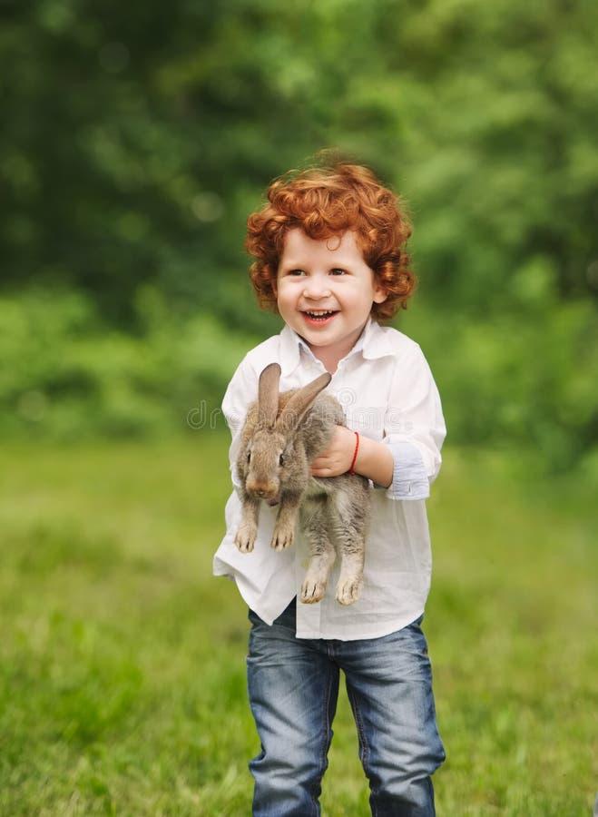Litle男孩戏剧用兔子在公园 库存图片