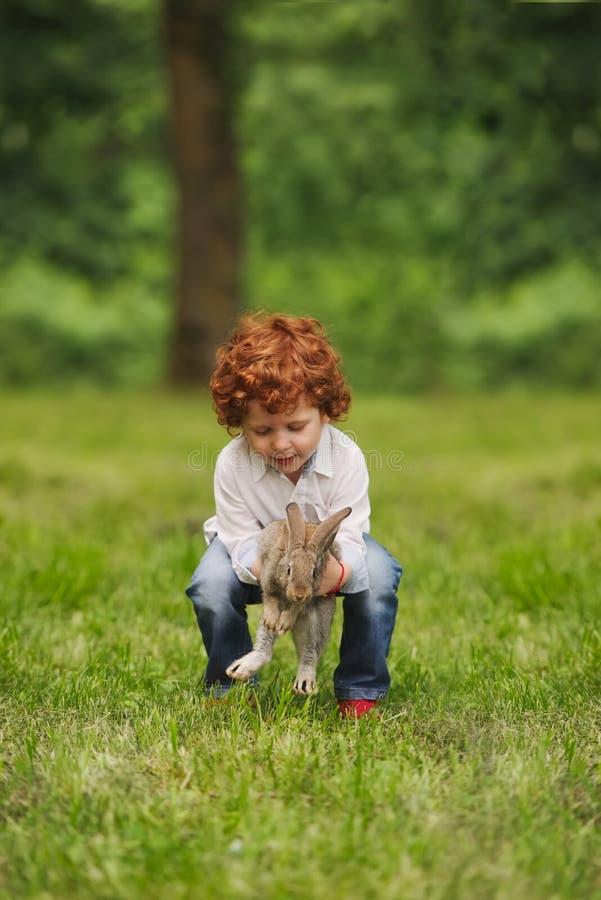 Litle男孩戏剧用兔子在公园 免版税图库摄影