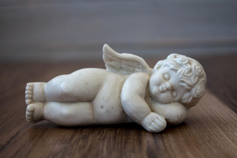 A litle angel on a wooden background stock photos