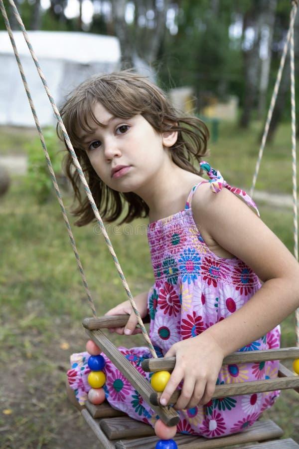 Litle girl sitting on swing