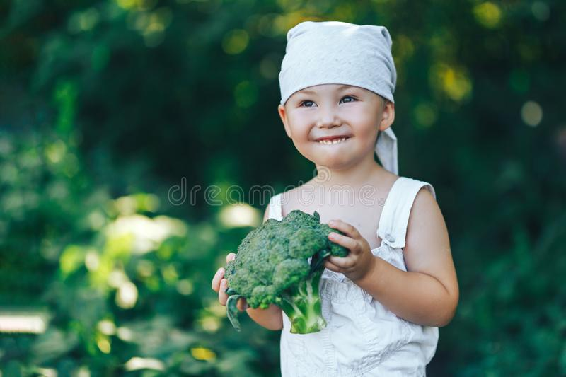 Litle happy smiling farmer boy in white overalls and grey hairband holding fresh organic broccoli in hands. garden, harvest season royalty free stock photography