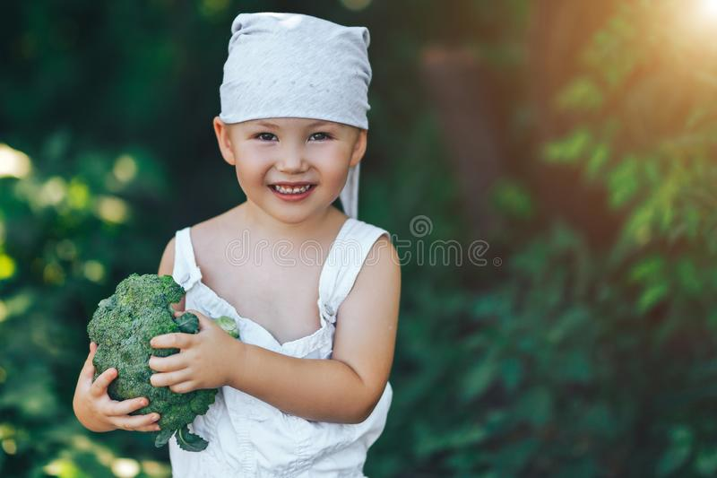 litle happy smiling farmer boy in white overalls and grey hairband holding fresh organic broccoli in hands. garden, harvest season royalty free stock images