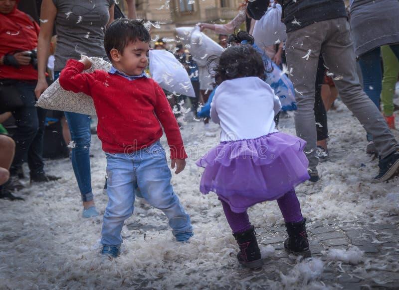 Litlle barn som slåss med kudden royaltyfri bild