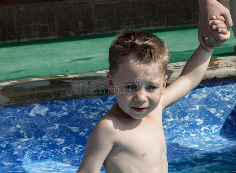 The litlle boy holds his mother hand in the pool royalty free stock photography