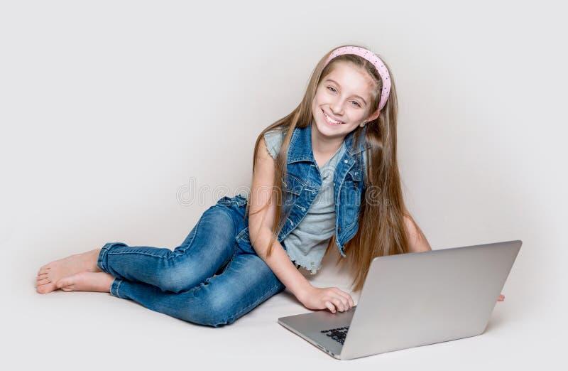 Litlle flicka som ligger på golv med bärbara datorn royaltyfria foton