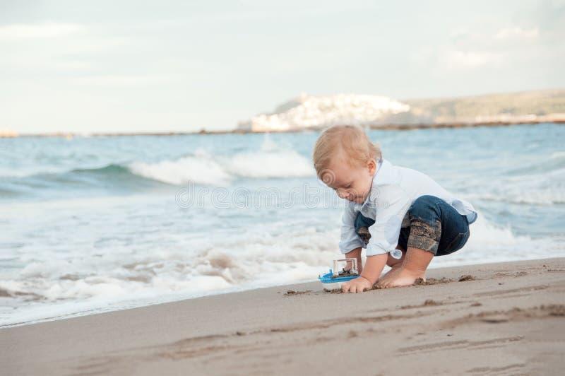Litlle pojke som spelar på stranden med ett skepp Sommarsemester och royaltyfri foto