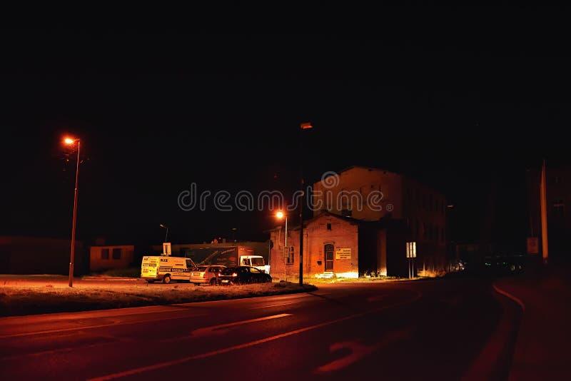 Litomerice, Tsjechische republiek - 14 Juli, 2018: asfaltweg die rond de oude historische industriële bouw en geparkeerde auto's  stock foto's