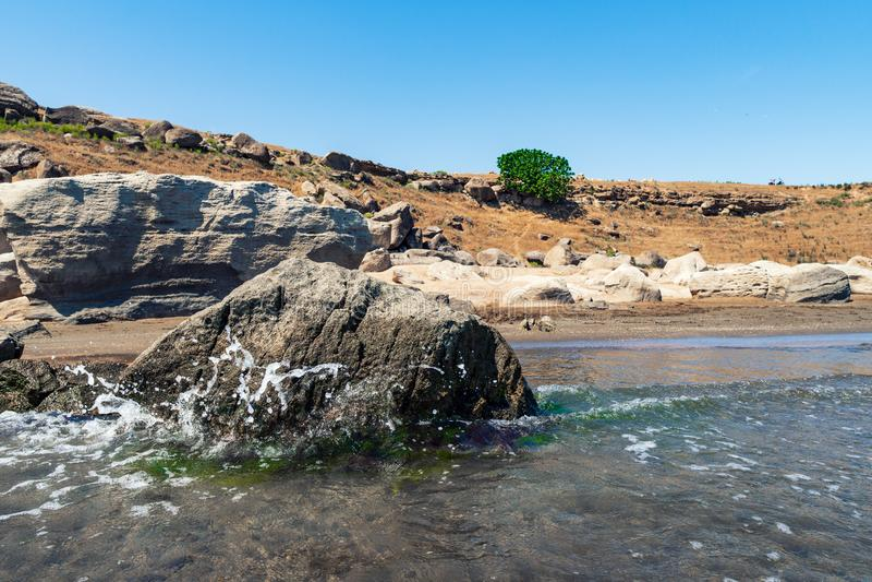 Litoral rochoso com água e as ondas claras foto de stock royalty free