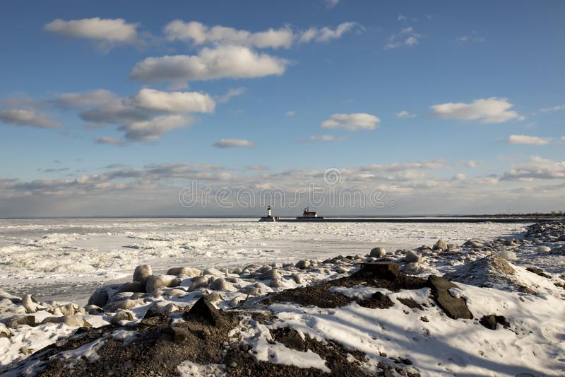 Litorale congelato roccioso del lago Superiore con i fari e lo shippi immagini stock libere da diritti