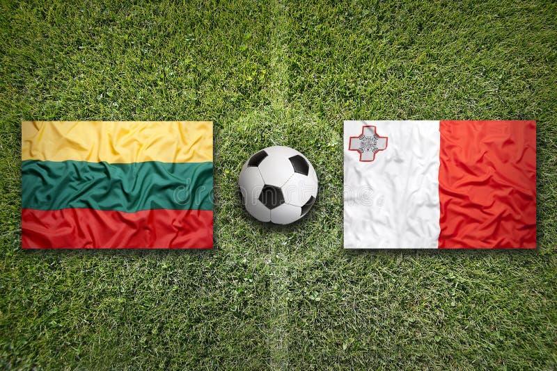 Litouwen versus De vlaggen van Malta op voetbalgebied stock foto