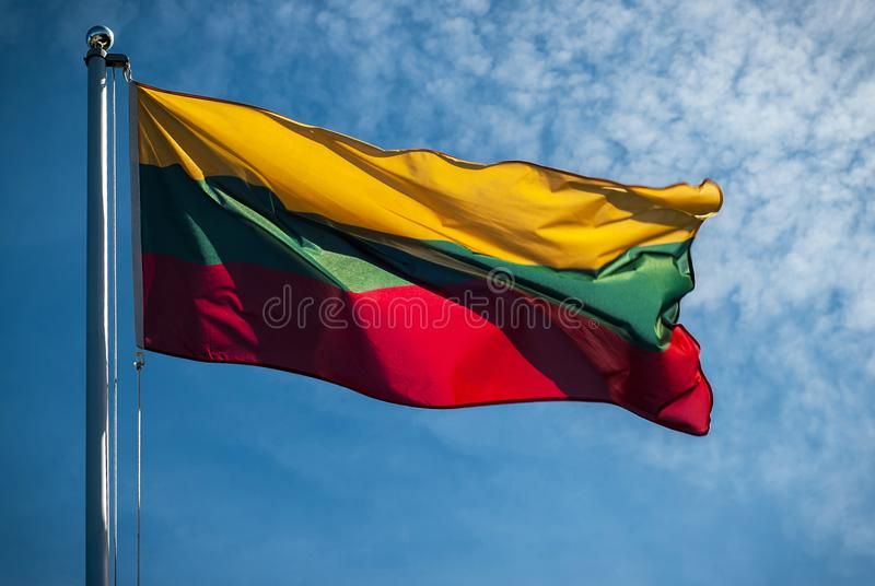 Litouwse nationale vlag met blauwe hemel op achtergrond stock fotografie